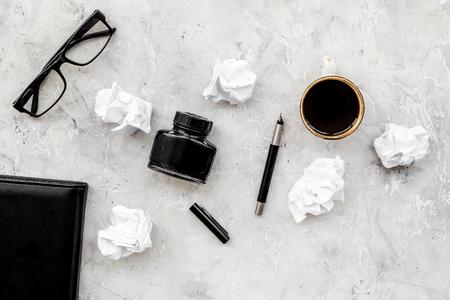 Notizbuch, Tinte, Badfeder, Kaffee, Gläser für Verfasserarbeitsplatz stellten auf graues Draufsichtmodell des Steinschreibtischhintergrundes ein Standard-Bild - 98089267