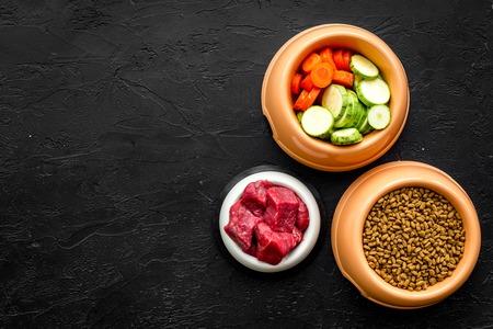 검은 책상 배경에 개를 먹이 플라스틱 그릇에 신선한 야채와 고기 건조 유기농 애완 동물 음식 상위 뷰를 조롱