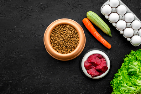 Dry pet food with natural ingredients. Raw meat, vegetables zucchini and carrot, eggs on black table background top view mock-up. Stok Fotoğraf