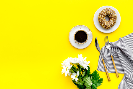Holiday lunch for woman with cup of americano, donut and flowers on yellow table background top view mock up