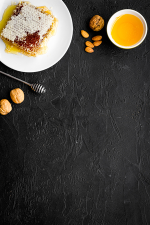 Fresh honey as dessert. Honey in bowl, honeycomb, nuts on black table top view copy space