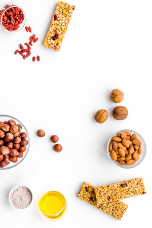 Make hearty granola bars with oatmeal, nuts, honey and berries. White background top view copy space