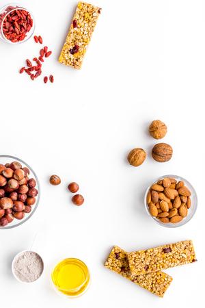 Prepara abbondanti barrette di cereali con farina d'avena, noci, miele e frutti di bosco. Spazio bianco della copia di vista superiore del fondo Archivio Fotografico - 98171707