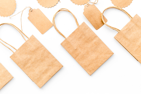 Brown kraft paper bag for shopping near price tags on white background top view mockup 版權商用圖片