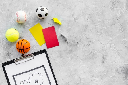 Sport judging concept. Sport game referee. Tactic plan for game, balls, red and yellow cards, whistle on stone background top view.