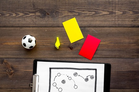 Sport judging concept. Soccer referee. Tactic plan for game, football ball, red and yellow cards, whistle on wooden background top view. Stock Photo