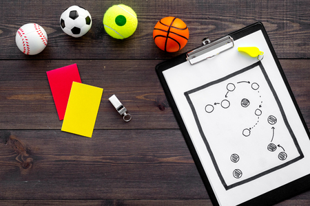 Sport judging concept. Sport game referee. Tactic plan for game, balls, red and yellow cards, whistle on wooden background top view.