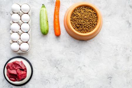 돌 책상 배경에 개를 먹이를위한 플라스틱 그릇에 신선한 야채, 계란, 고기와 마른 유기농 애완 동물 음식 상위 뷰를 조롱 스톡 콘텐츠