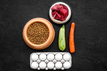천연 성분으로 건조한 애완 동물 사료. 생고기, 야채 호박, 당근, 블랙 테이블 backgroud 평면도 모의에 계란.