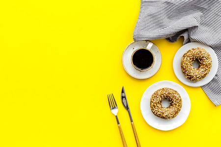 woman desk with flowers, coffee and donuts for breakfast in spring desing on yellow background flat lay mock-up
