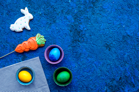 Easter celebration with colorful eggs and gingerbread in shape of easter bunny and carrot. Blue background top view mock up.
