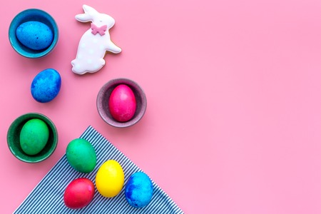 Easter celebration with colorful eggs and gingerbread in shape of easter bunny and carrot. Pink background top view mock up.