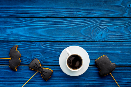 Mens birthday celebration concept. Cookies in shape of moustache, hat, bow tie near coffee on blue wooden background top view. Zdjęcie Seryjne