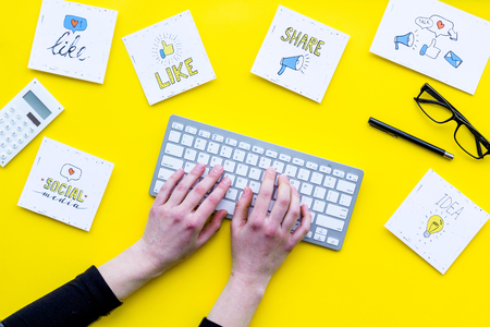 Social media promotion. Work desk with socail media icons. Yellow background top view.
