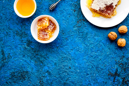 Fresh honey as dessert. Honey in bowl, honeycomb, nuts on blue table top view.