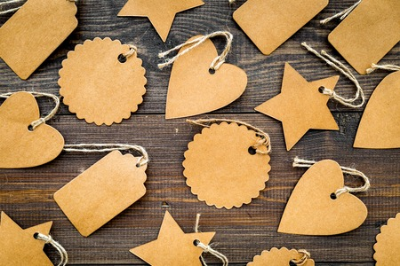 Figured blank tags for write price or discount on dark wooden background. Stock fotó