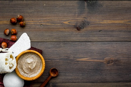 Homemade spa with organic scrub and hazelnut on wooden background top view space for text.