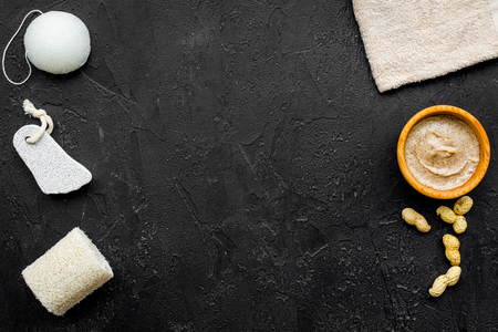 organic scrub with peanut for homemade spa on black table background top view mockup Stock Photo