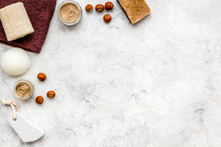 Beauty set with natural hazelnut scrub for spa on stone desk background top view mockup