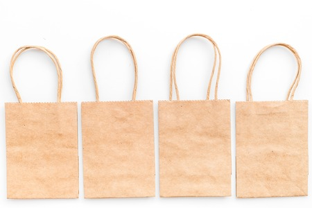 Brown kraft paper bag for shopping on white background top view.