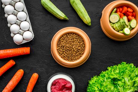 검은 책상 배경에 개를 먹이기위한 플라스틱 그릇에 신선한 야채, 계란, 고기와 함께 마른 유기농 애완 동물 음식 상위 뷰를 조롱