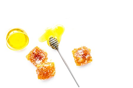 Honey background. Honey dipper and honeycomb on white background top view. Banco de Imagens