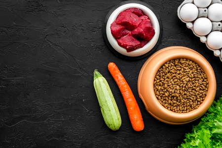 Pet care with dry food, vegetables and raw meat for dog or cat in plastic bowl on black desk background top view space for text