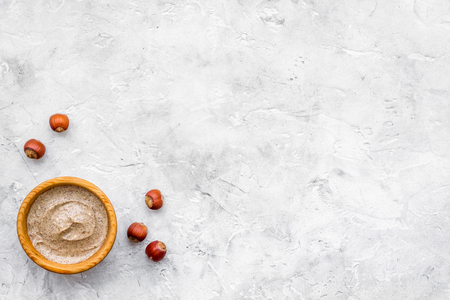 Organic scrub with hazelnut for homemade spa on stone table background top view mockup
