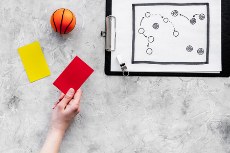 Sport judging concept. Basketball referee. Tactic plan for game, basketball ball, red and yellow cards, whistle on stone background top view copy space. Stock Photo