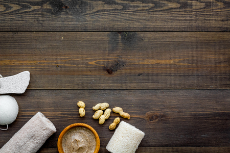 Organic scrub with peanut for homemade spa on wooden table background top view mockup