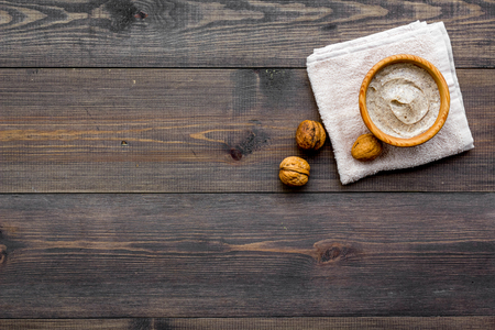 Organic scrub with walnut for homemade spa on wooden table background top view mockup