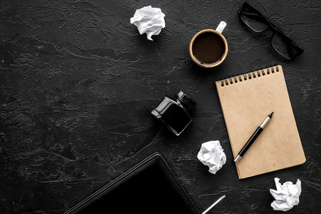 Retro and modern writer desktop with cup of coffee, notebook and ink on black table background top view mock up