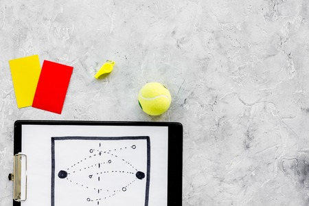 Sport judging concept. Tennis referee. Tactic plan for game, tennis ball, red and yellow cards, whistle on stone background top view copy space.