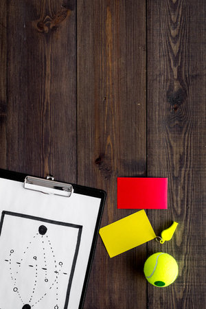 Sport judging concept. Tennis referee. Tactic plan for game, tennis ball, red and yellow cards, whistle on wooden background top view, Stock Photo