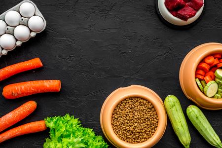 천연 성분으로 건조한 애완 동물 사료. 생고기, 야채 호박과 당근, 계란 검은 테이블 배경 평면도 목업. 스톡 콘텐츠