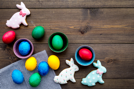 Easter celebration with colorful eggs and gingerbread in shape of easter bunny and carrot. Wooden background top view mock up.