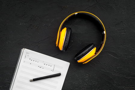 Work desk of modern composer. Music notes near headphones on black background top view.