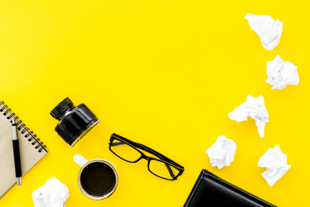 Writer office desk with notebook, ink, pen and glasses on yellow background top view space for text