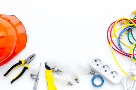 Electrician work concept. Hard hat, tools, cabel, socket outlet on white background top view space for text