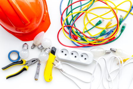 Electrician work concept. Hard hat, tools, cabel, socket outlet on white background top view Imagens