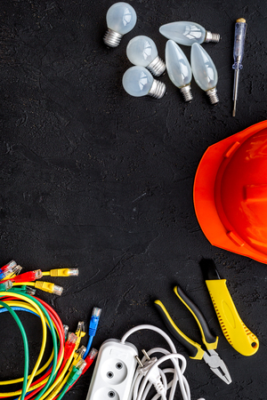Electrician work concept. Hard hat, tools, cabel, bulb, socket outlet on black background top view space for text Imagens