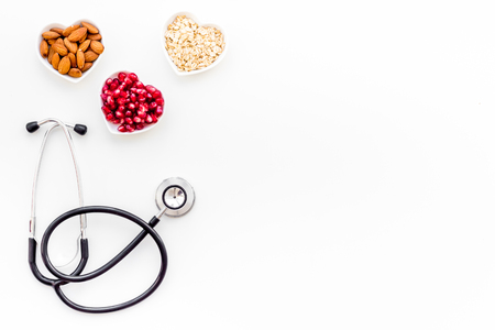 Oatmeal, pomegranate, almond in heart shaped bowl near stethoscope on white background top view copy space
