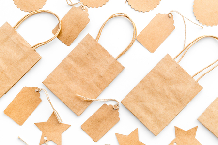 Bruine kraftpapier-zak voor het winkelen dichtbij prijskaartjes op wit achtergrond hoogste meningsmodel