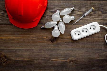 Electrical installation, wiring work concept. Hard hat, bulb, socket outlet on dark wooden background top view copy space