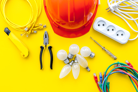 Electrician work concept. Hard hat, tools, cabel, bulb, socket outlet on yellow background top view