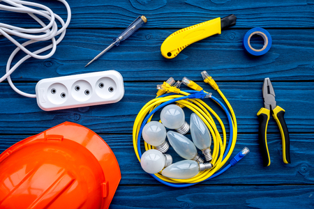 Electrician work concept. Hard hat, tools, cabel, bulb, socket outlet on blue wooden background top view Imagens