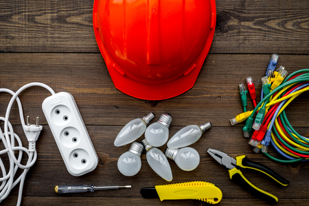 Electrician work concept. Hard hat, tools, cabel, bulb, socket outlet on dark wooden background top view