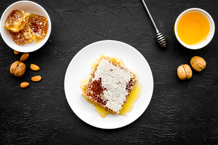 Fresh honey as dessert. Honey in bowl, honeycomb, nuts on black table top view. Stock Photo
