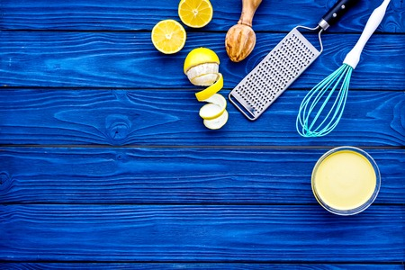 Cook lemon curd. Sweet cream in bowl, fruits, kitchen utensils grater and whisk on blue wooden background top view.