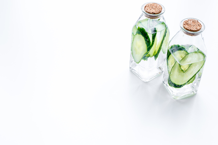 Drink for weight loss. Water with cucumber on white background top view. Фото со стока